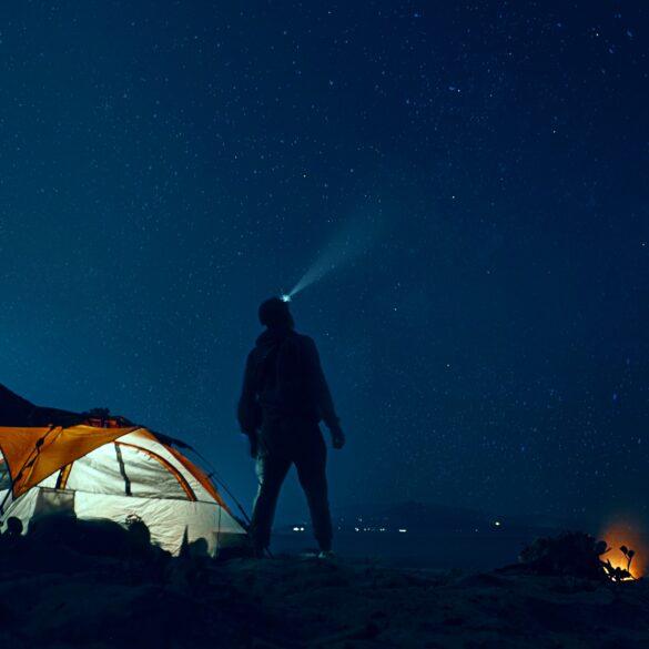ragazzo guarda il cielo con torcia luminosa in testa